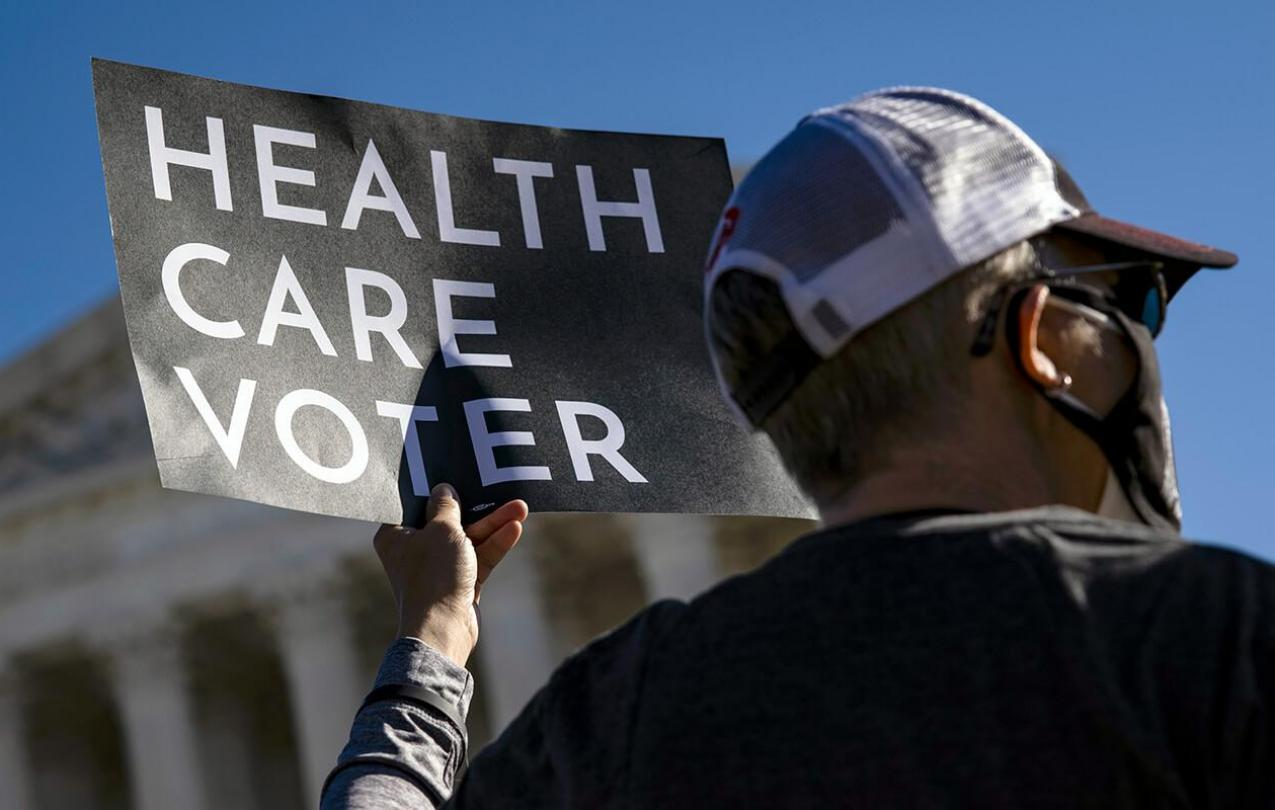 Health care voter holding up a sign